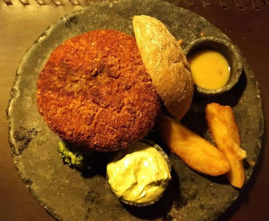 Cidade Baixa: Hamburguer bovino de 160g recheado de queijo cacciocavalo e castanha de caju empanado, maionese de manjericão, alface chifonet no pão australiano com cebola crispy de acompanhamento.
